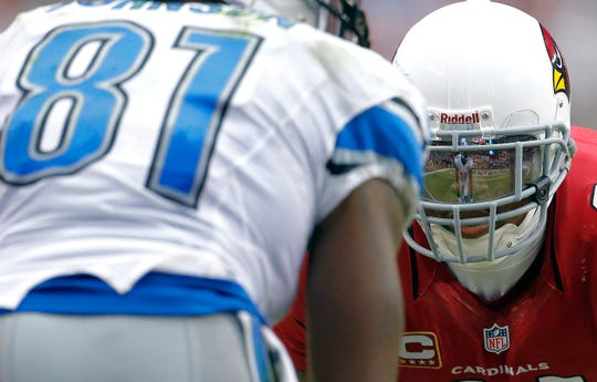 Detroit Lions wide receiver Calvin Johnson is reflected in the face mask of Arizona Cardinals defensive back Patrick Peterson on Sunday, Sept. 15, 2013, in Glendale.