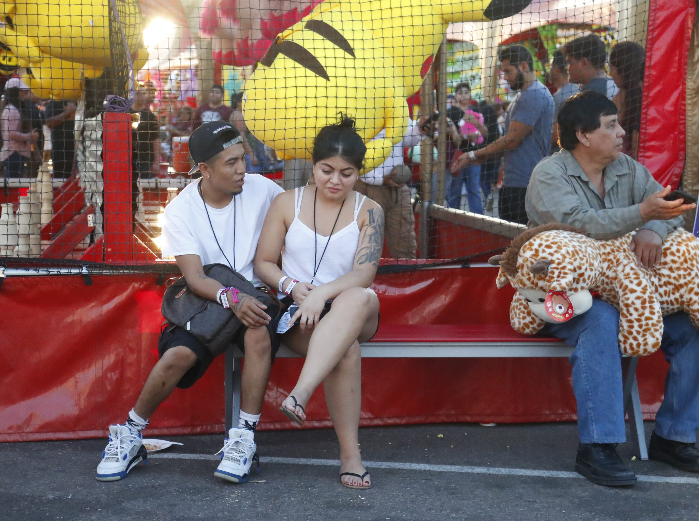 Fair-goers grab a seat waiting for friends or family at the Arizona State Fair in Phoenix, Ariz. on October 21, 2018.