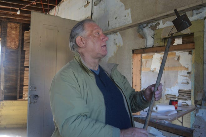 Lou Hebert talks about a G.A.R. parade torch discovered in the neglected Heritage Hall during renovations.  Several artifacts, including old banners and posters, were found in the walls and attic.
