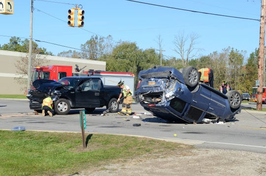 Crews clean up the intersection of Dove and Michigan roads after a two-car rollover crash on Oct. 22, 2018.