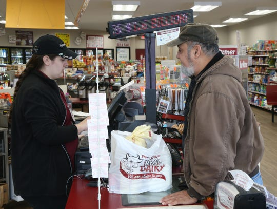 Manny Pabon of Poughkeepsie purchases his Mega Million lotto ticket from Kaitlyn VanWagenen at the Vassar Road Stewart's in the Town of Poughkeepsie on October 22, 2018.