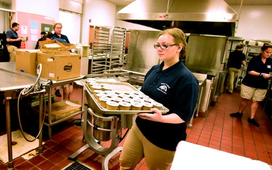 West York Area High School junior Lindsey Mauss works in the school's cafeteria during a lunch period Monday, Oct. 15, 2018. She works in a program offered by the state's Office of Vocational Rehabilitation in which students with disabilities can be employed through the high school in cafeteria positions. These students receive training using a job coach to prepare them for the workforce after graduation. Bill Kalina photo