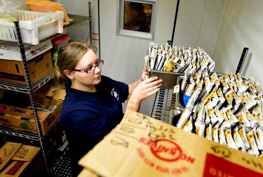 West York Area High School junior Lindsey Mauss sorts food in a cooler in the school's cafeteria during a lunch period Monday, Oct. 15, 2018. She works in a program offered by the state's Office of Vocational Rehabilitation in which students with disabilities can be employed through the high school in cafeteria positions. These students receive training using a job coach to prepare them for the workforce after graduation. Bill Kalina photo