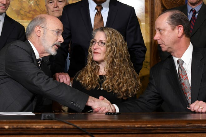 Pennsylvania Gov. Tom Wolf of Pennsylvania shakes hands with Jim Piazza after signing anti-hazing legislation inspired by Piazza's son, Penn State student Tim Piazza who died after a night of drinking in a fraternity house, Friday, Oct. 19, 2018 in Harrisburg, Pa. Sitting between them is Evelyn Piazza, the mother of Tim Piazza. (AP Photo/Marc Levy)