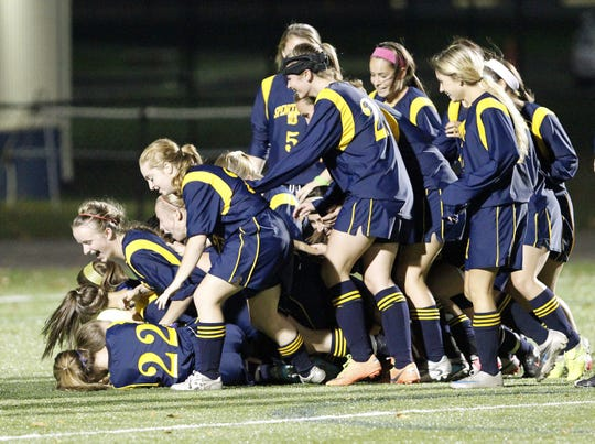 Spencerport's Katie Chamberlain, top left, and her Ranger teammates pile on their goalkeeper after the Rangers beat Rush-Henrietta Thursday. Spencerport won the Class AA first round game, 3-0.
