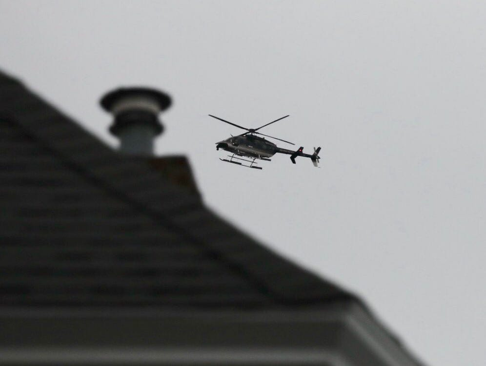 A helicopter hovers while police investigate a double homicide in Sodus.