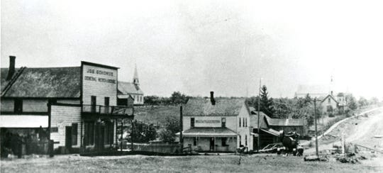 Main road through Shaw, Oregon circa 1909.  Left to right, Schomus General Store, Waldo Hills Hotel and the Catholic church.  The Methodist church is also visible in the background.