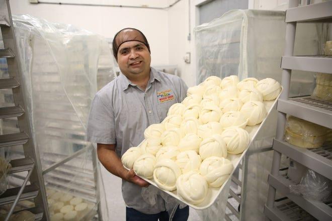 Francisco Ochoa, owner of Ochoa's Queseria, holds a tray of fresh cheese at his store on Thursday, Oct. 18 in Albany.