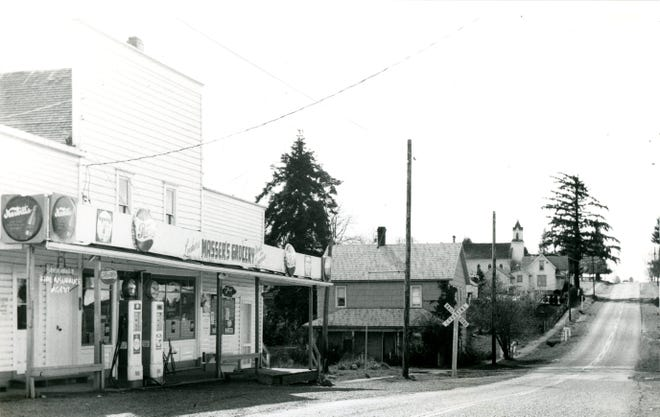 Main road through Shaw, Oregon circa 1962. Left to right, Masser's Grocery Store, former Waldo Hills Hotel now a private residence, and the Catholic church up on the hill.