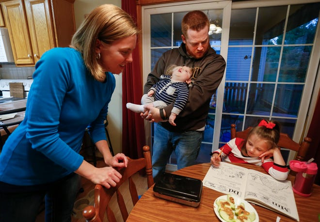 Tom Masterson holds one-year-old Owen as he and his wife Jessica help their daughter Ryleigh with homework at their home on Thursday, October 11, 2018. Owen was born missing the top part of his skull and was not expected to survive childbirth.