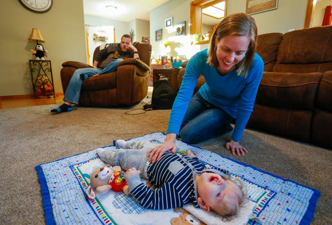 Jessica Masterson plays with one-year-old Owen on a mat at their home on Thursday, October 11, 2018. Owen was born missing the top part of his skull and was not expected to survive childbirth.