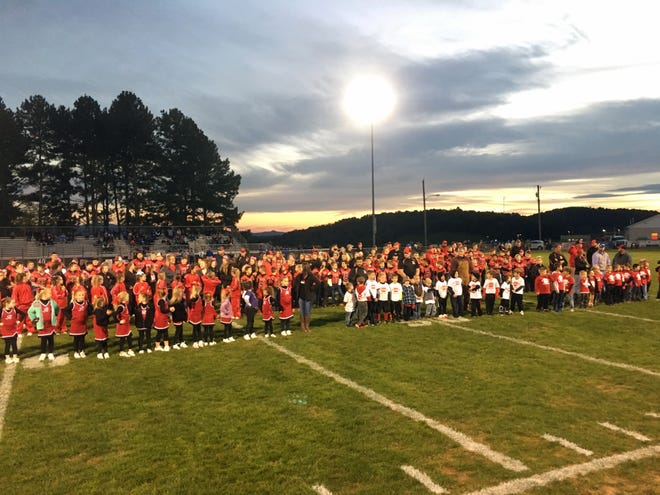 Players, cheerleaders and coaches for Riverheads Little League football program line up on the field while being honored prior to Riverheads High School's game Friday night against Robert E. Lee.