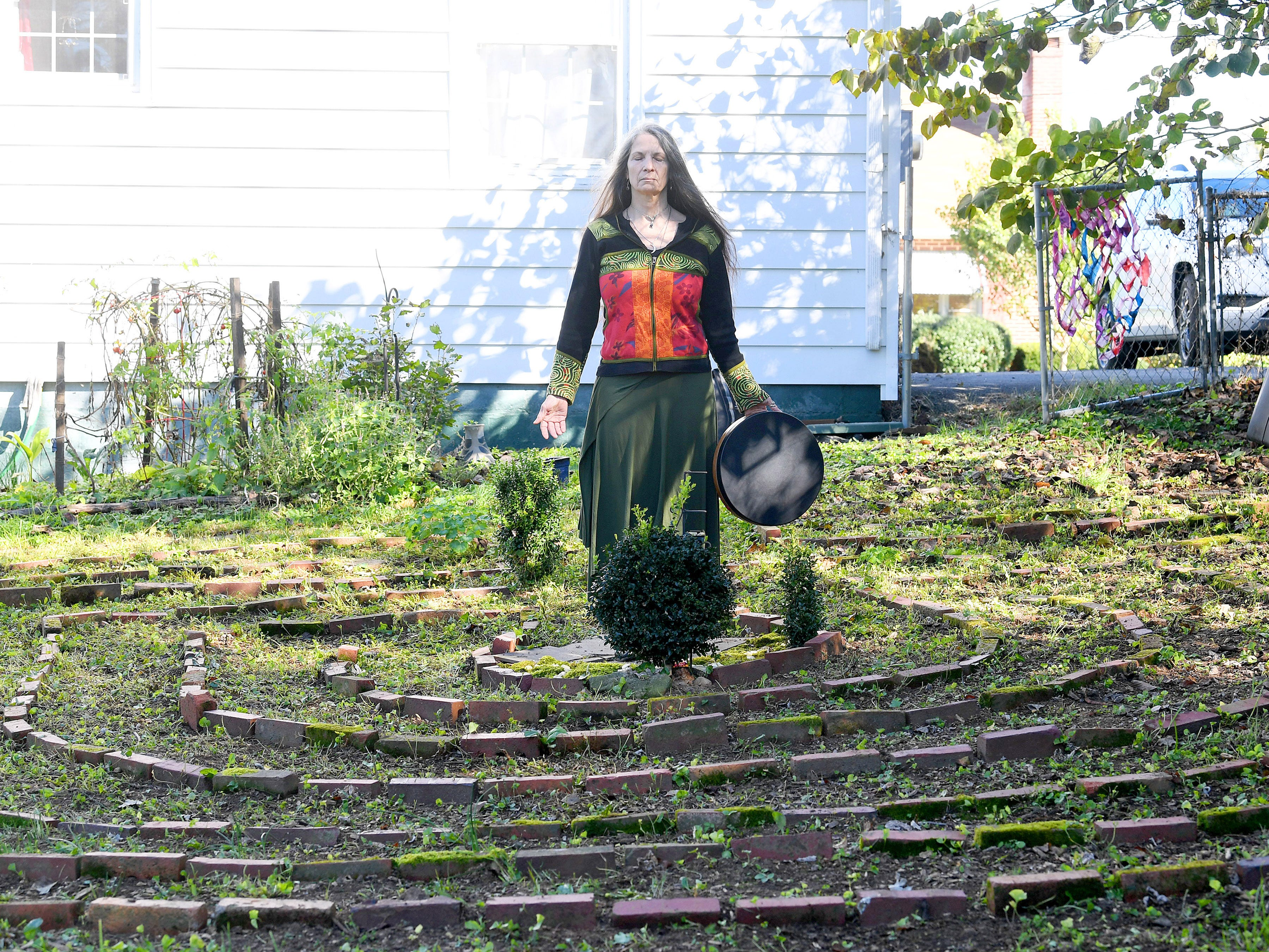 "Willow Kelly, a witch and Sufi, pauses at the heart of a labyrinth outside her Staunton residence on October 19, 2018. ""The labyrinth is a great mystery to me that I continue to explore with wonder,"" she says. ""I walk it daily with few exceptions."""