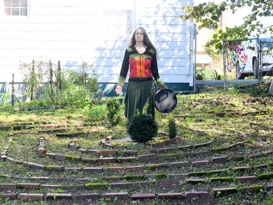 """Willow Kelly, a witch and Sufi, pauses at the heart of a labyrinth outside her Staunton residence on October 19, 2018. """"The labyrinth is a great mystery to me that I continue to explore with wonder,"""" she says. """"I walk it daily with few exceptions."""""""