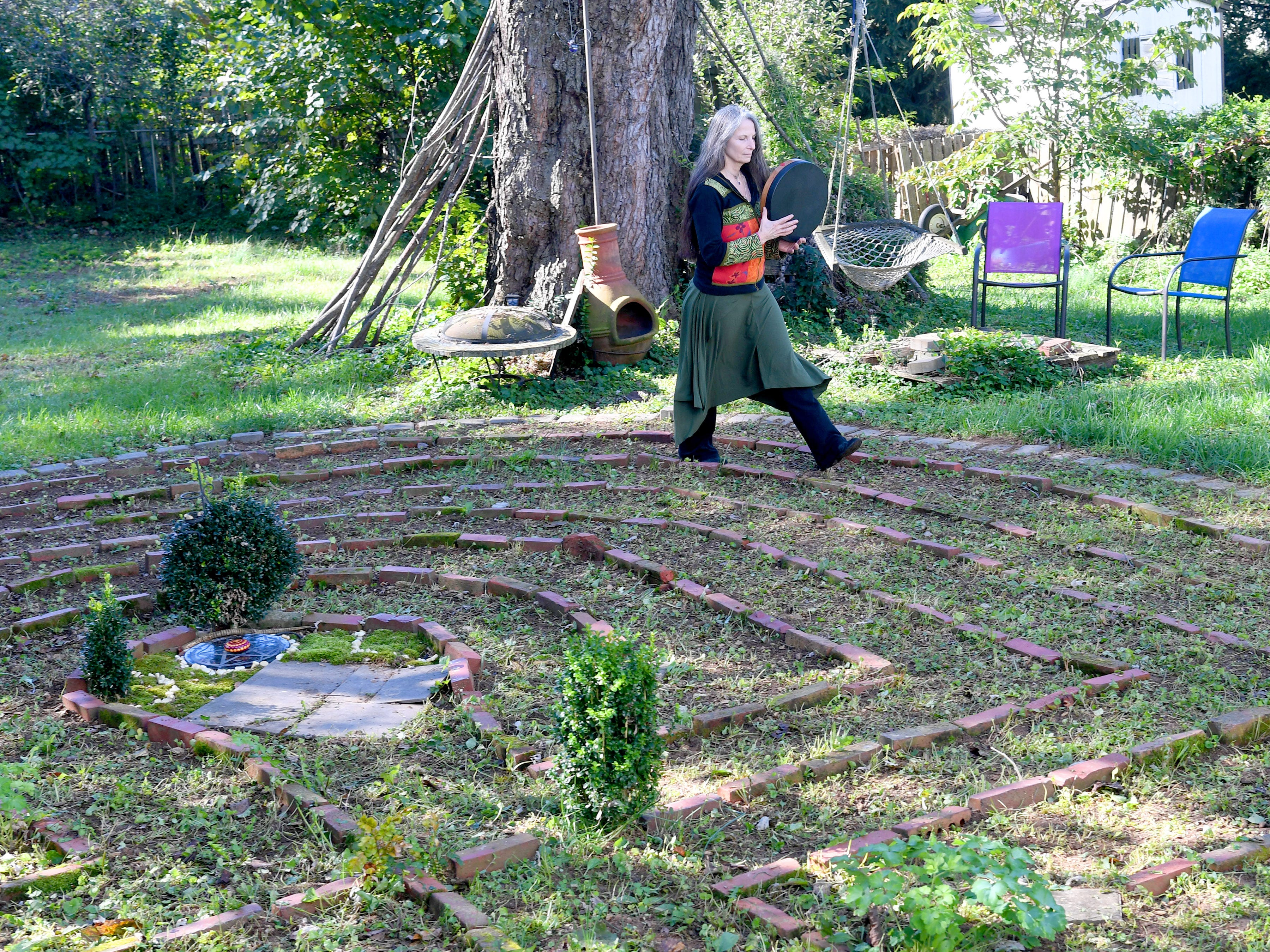 "Willow Kelly, a witch and Sufi, walks the pattern for her return journey after reaching the center of the labyrinth outside her Staunton residence with measured strides in time with her drum on October 19, 2018. ""The labyrinth is a great mystery to me that I continue to explore with wonder,"" she says. ""I walk it daily with few exceptions."""
