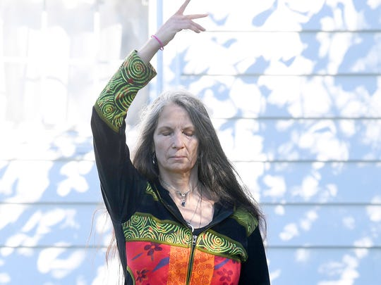 """The hands of Willow Kelly, a witch and Sufi, move in a prescribed pattern after reaching the heart of her labyrinth, outside her Staunton residence on October 19, 2018. """"I have a very complex spell (intention or affirmation if you prefer) that I do in the labyrinth,"""" she says. """"My movements are an embodiment of both sending those energies out into the world as well as calling them into myself there is a sustainable flow of energy moving our and coming in."""""""