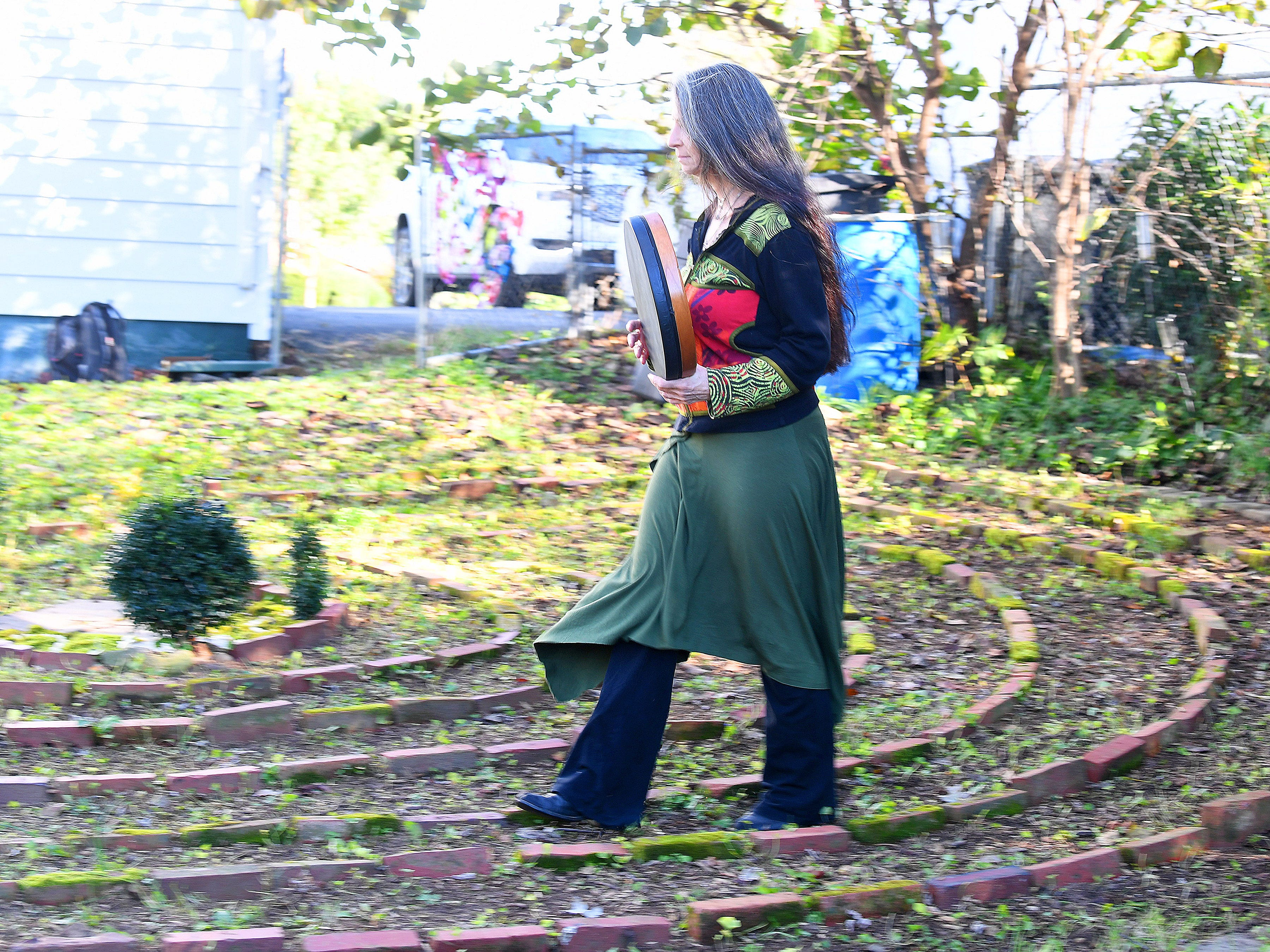 "Willow Kelly, a witch and Sufi, walks the pattern of a labyrinth outside her Staunton residence with measured strides in time with her drum on October 19, 2018. ""The labyrinth is a great mystery to me that I continue to explore with wonder,"" she says. ""I walk it daily with few exceptions."""