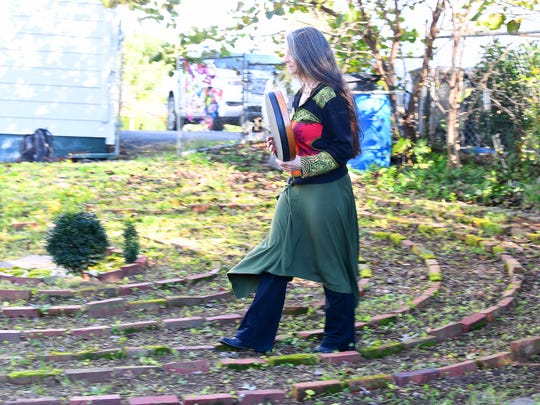 """Willow Kelly, a witch and Sufi, walks the pattern of a labyrinth outside her Staunton residence with measured strides in time with her drum on October 19, 2018. """"The labyrinth is a great mystery to me that I continue to explore with wonder,"""" she says. """"I walk it daily with few exceptions."""""""