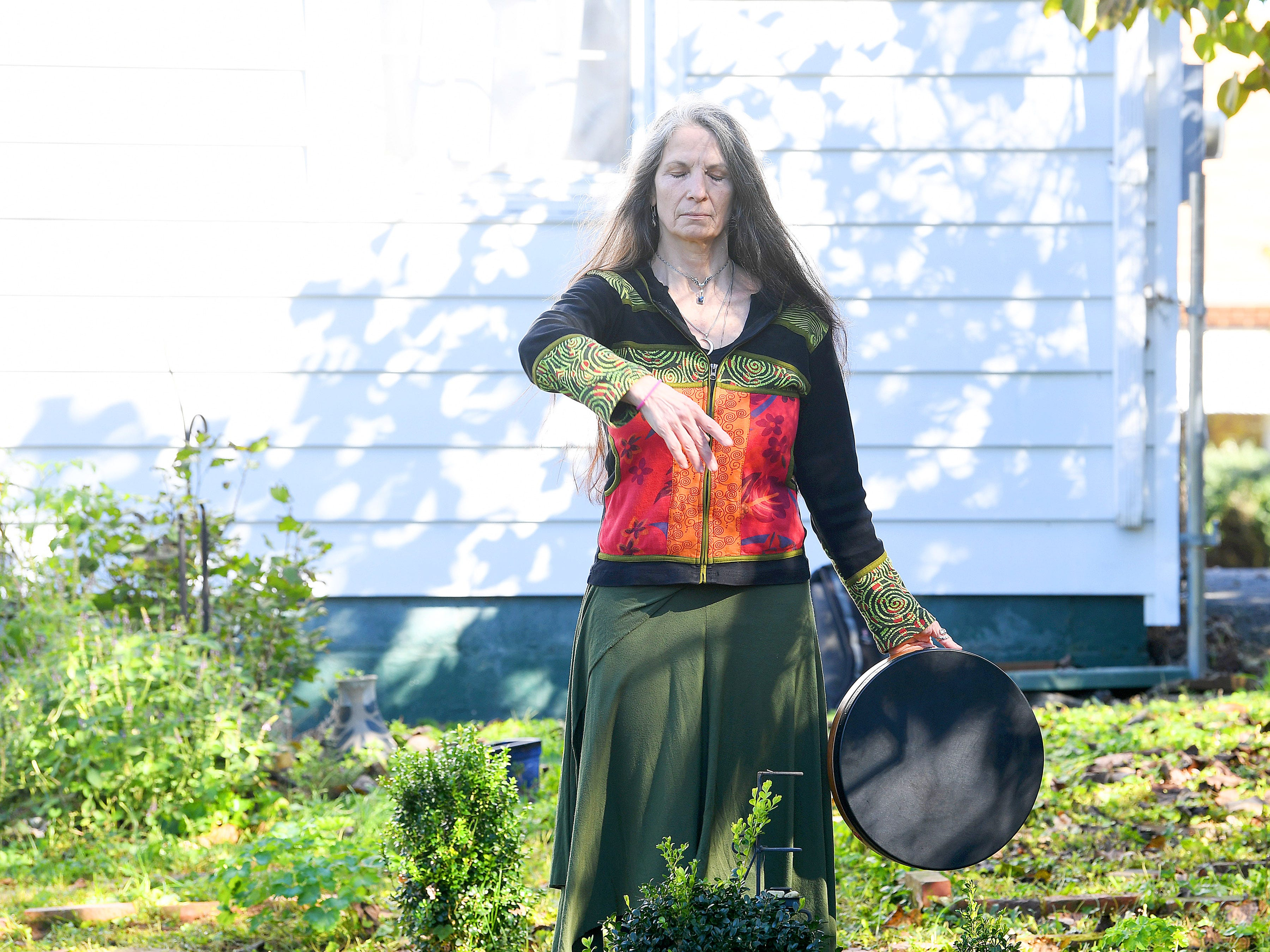 "The hands of Willow Kelly, a witch and Sufi, move in a prescribed pattern after reaching the heart of her labyrinth, outside her Staunton residence on October 19, 2018. ""I have a very complex spell (intention or affirmation if you prefer) that I do in the labyrinth,"" she says. ""My movements are an embodiment of both sending those energies out into the world as well as calling them into myself there is a sustainable flow of energy moving our and coming in."""