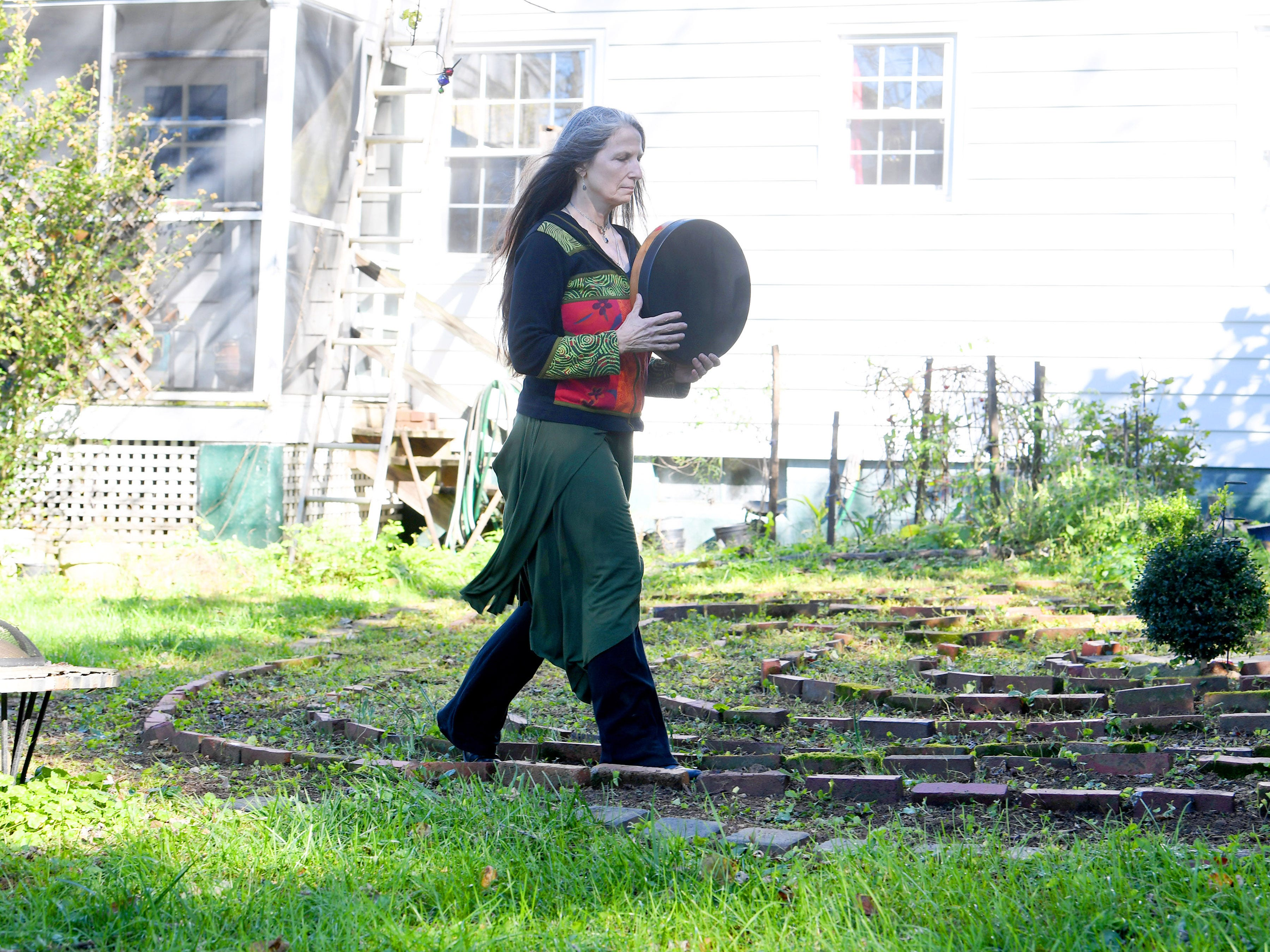 "Willow Kelly, a witch and Sufi, uses a middle eastern frame drum as she walks the pattern of a labyrinth outside her Staunton residence on October 19, 2018. She says it alters brainwave patterns using high and low frequencies. ""Many spiritual traditions around the world use them and rightfully so."""