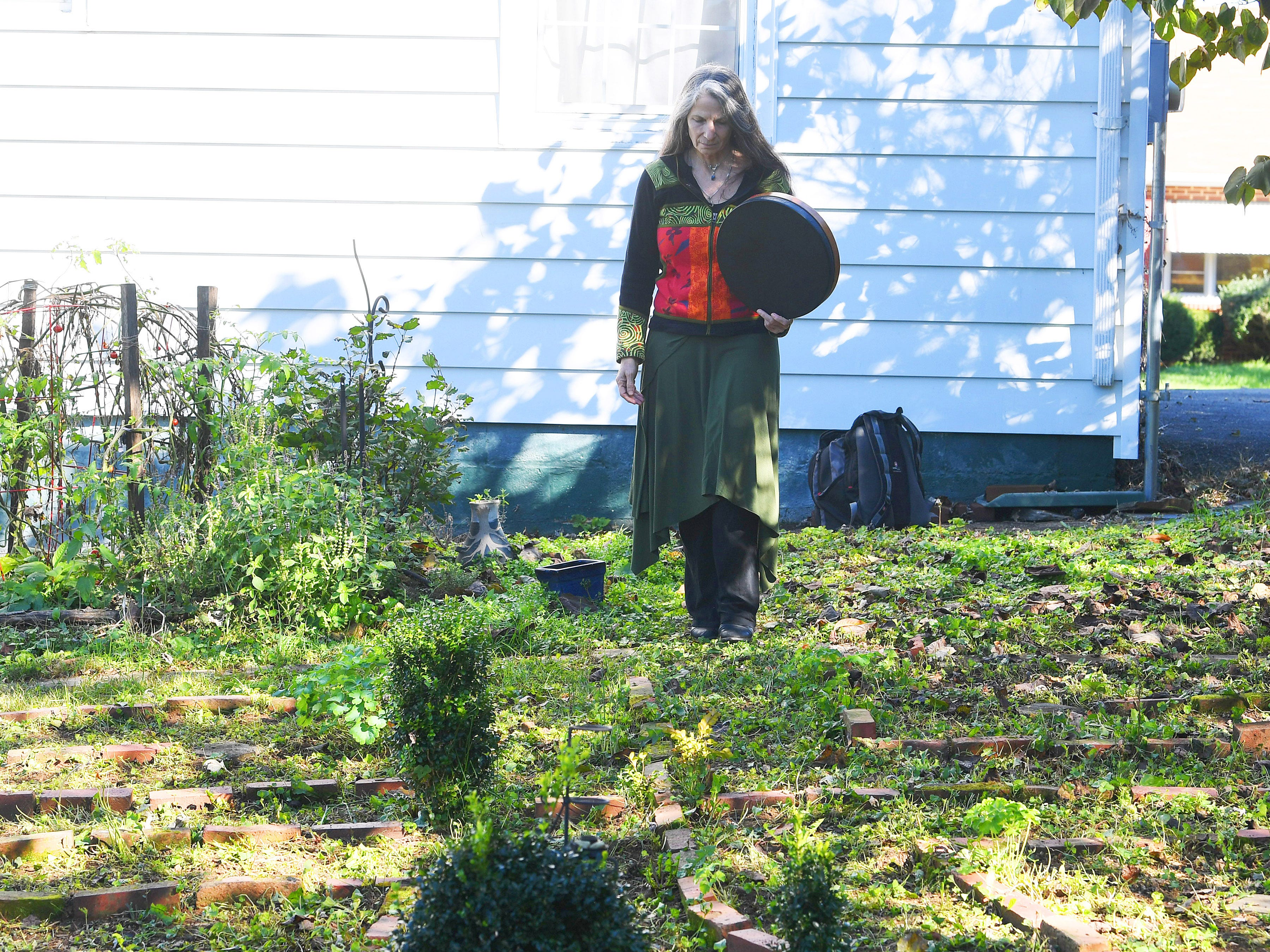 "Willow Kelly, a witch and Sufi, prepares to enter the pattern of a labyrinth outside her Staunton residence on October 19, 2018. ""The labyrinth is a great mystery to me that I continue to explore with wonder,"" she says. ""I walk it daily with few exceptions."""