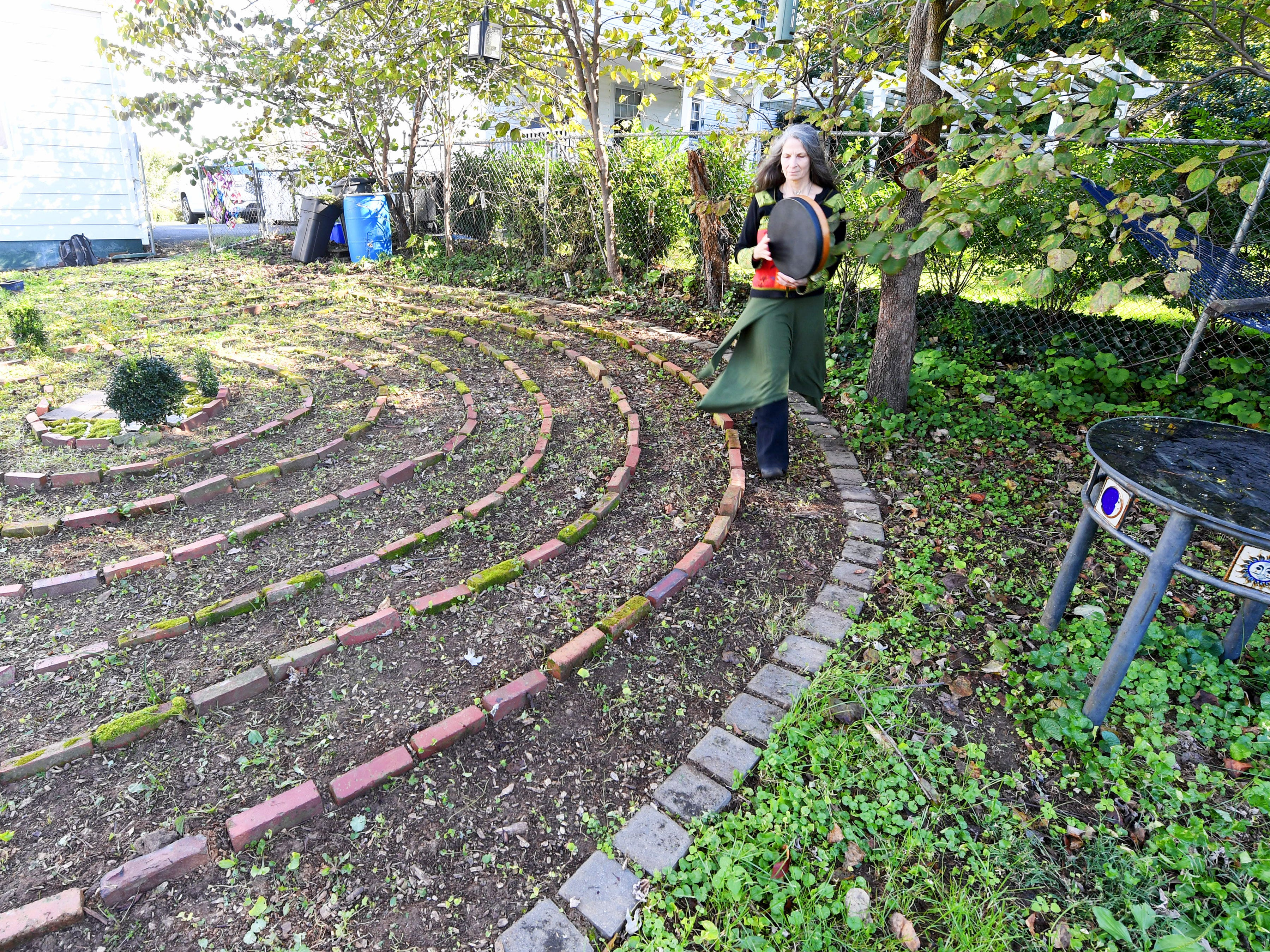 "Willow Kelly, a witch and Sufi, maintains measured strides as she walks one of circuits of the pattern of a labyrinth outside her Staunton residence on October 19, 2018. ""When I'm not home, I can walk it anywhere or trace the pattern with my finger,"" she says. ""I also have a fabric finger labyrinth I sometimes travel with."""