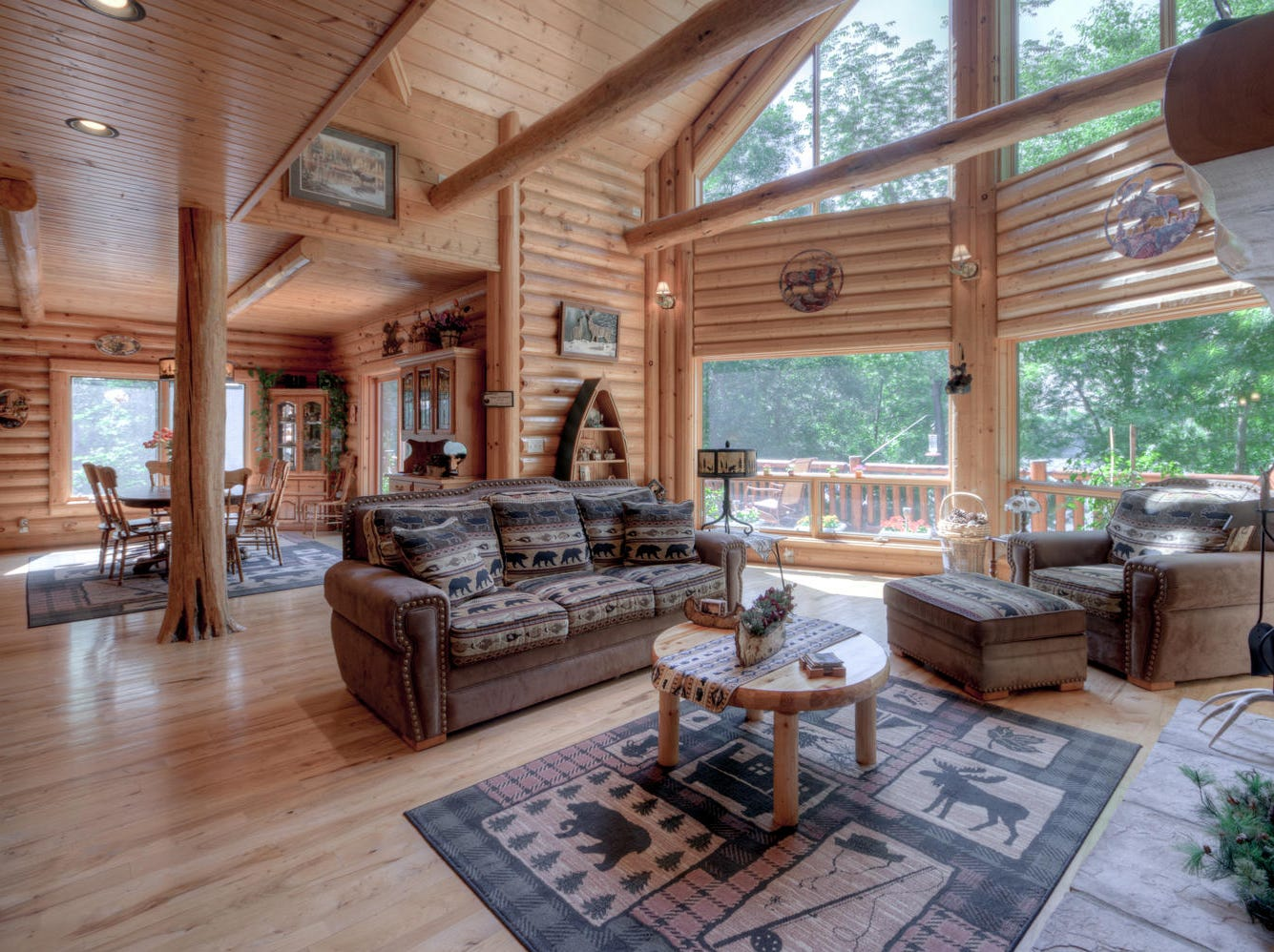 Just inside the entry the vaulted, exposed beam ceilings of the great room soar overhead and a wall of picture windows look out to the lake.