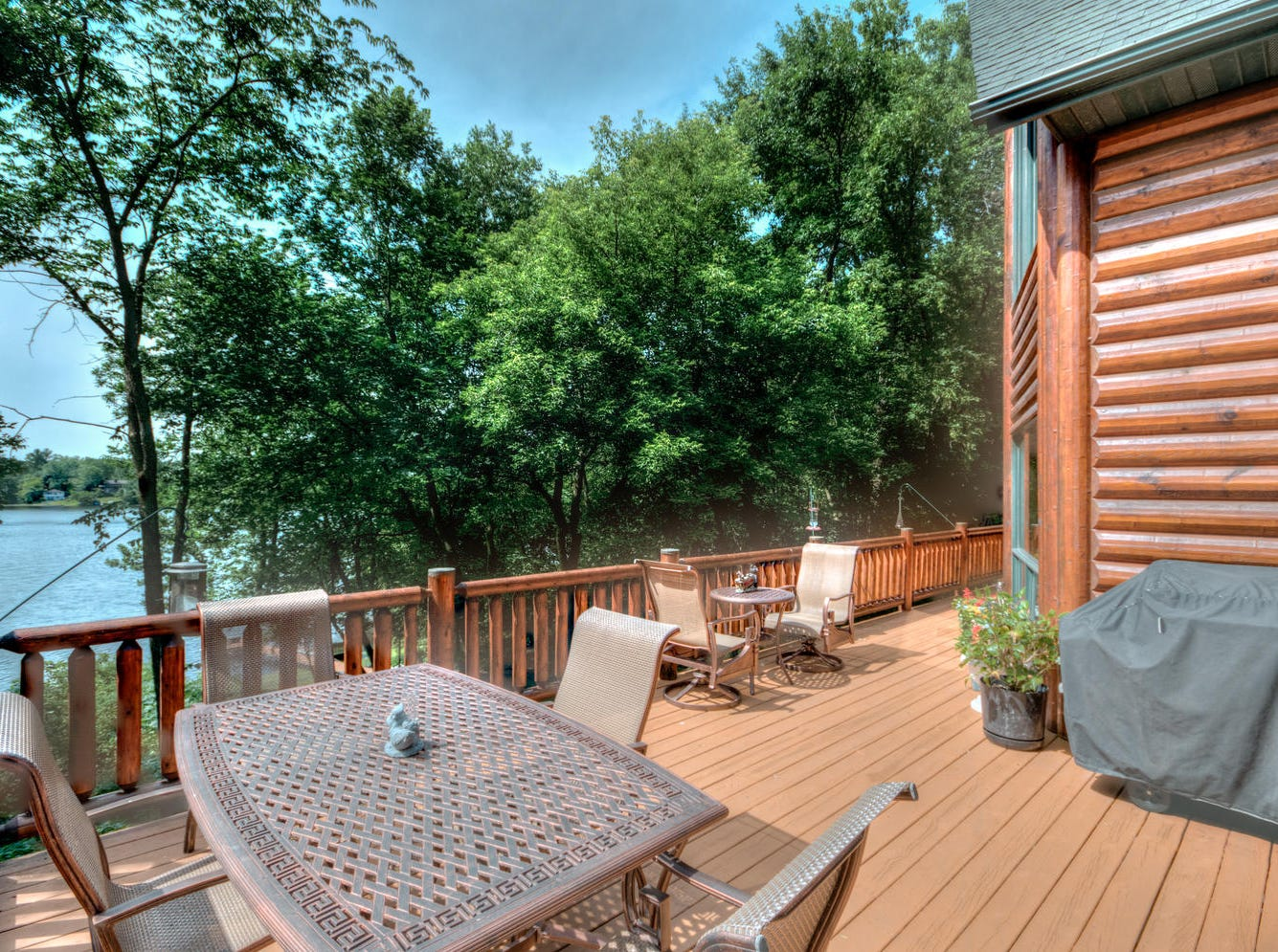 The waterfront can be viewed from the generous second-story deck complete with a log railing, which also spans the length of the house
