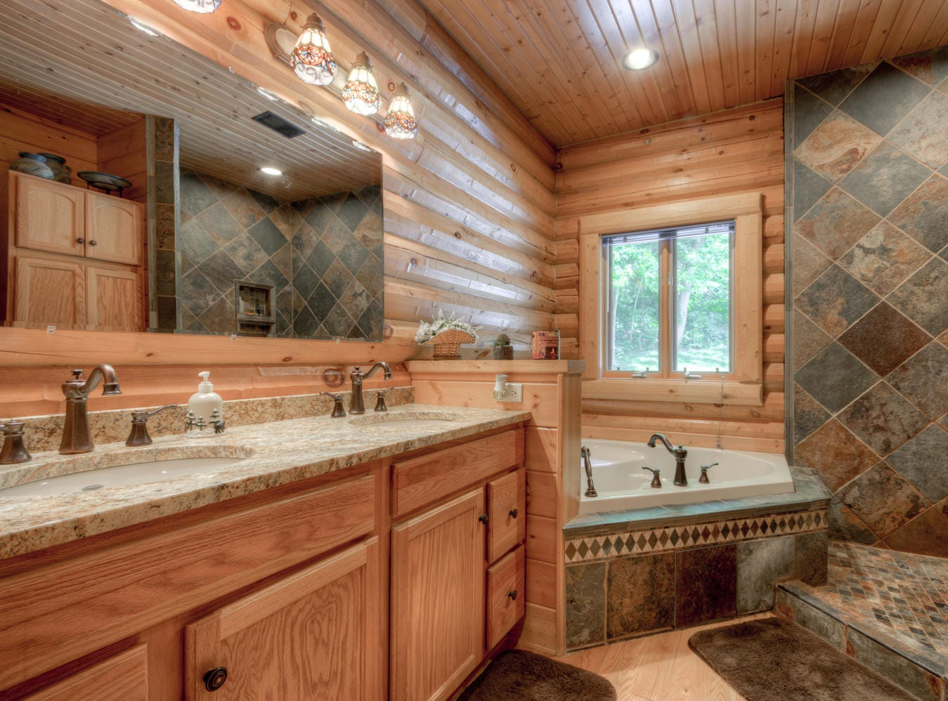 The en suite is finished with a double vanity, jetted tub and an open walk-in shower.