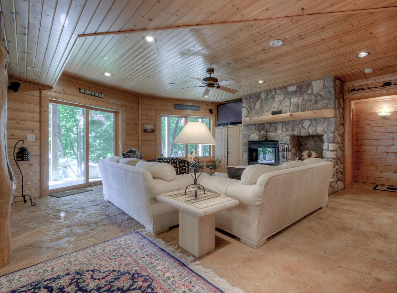 The lower level includes a family room complete with a stone fireplace and a sliding glass door to access the lake.