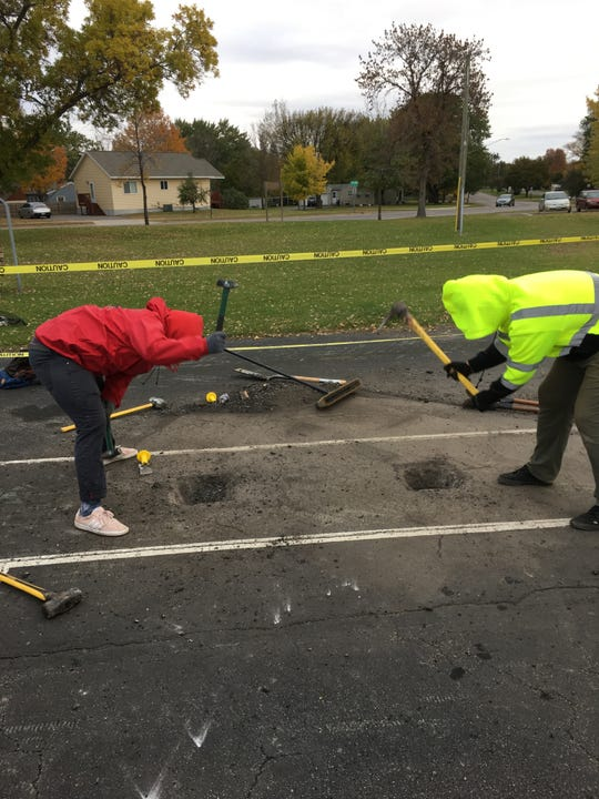 Jesse Landowski, left, helps Isaac Hubbard take sledgehammers to the tennis court at Highway Park, where Hubbard is installing a temporary skate park. Landowski and Hubbard were both regulars at the Heritage Park skate park before it was demolished.