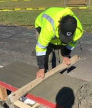 Isaac Hubbard works on constructing a concrete obstacle for the temporary skate park he's helping to install in St. Cloud.