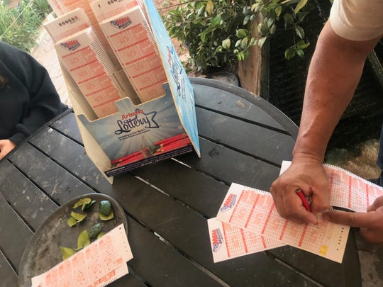 Customers fill out lottery tickets outside the Beaver Dam Station in Arizona on Monday. Many said they had made the trip to the Arizona Strip specifically to take part in the Mega Millions lottery.