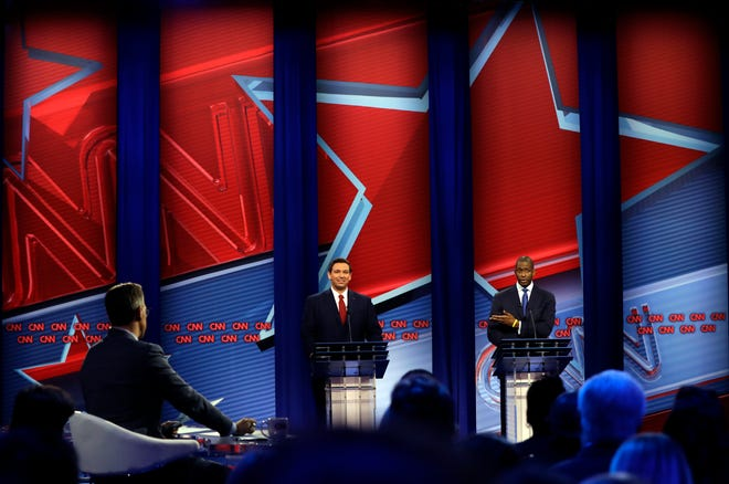 Florida Republican gubernatorial candidate Ron DeSantis, center, and his Democratic opponent Andrew Gillum, right, participate in a CNN debate moderated by Jake Tapper on Oct. 21 in Tampa.