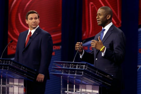 Florida Democratic gubernatorial candidate Andrew Gillum, right, speaks as Republican gubernatorial candidate Ron DeSantis looks on during a CNN debate Oct. 21, 2018, in Tampa.