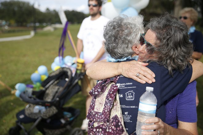 Margie Marcil, left, is hugged by Cheryl Burnett after their group gathered to walk in honor of Marcil's late husband, who passed in 2015, at the 2015 Alzheimer's Project Forget Me Not Walk at Cascades Park. This year's walk is set for Nov. 4.
