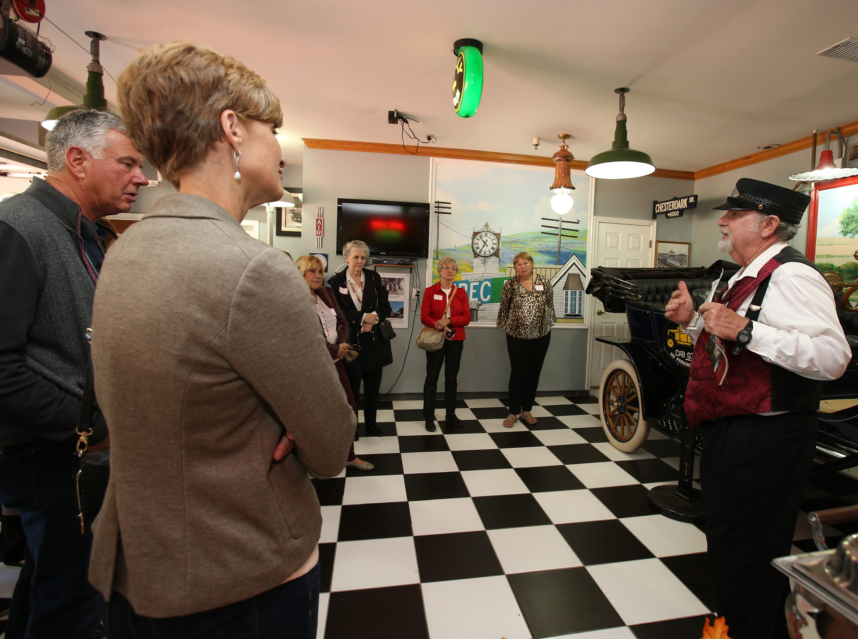 Mike Newlon shows guests his garage where he keeps vintage cars and gas pumps.