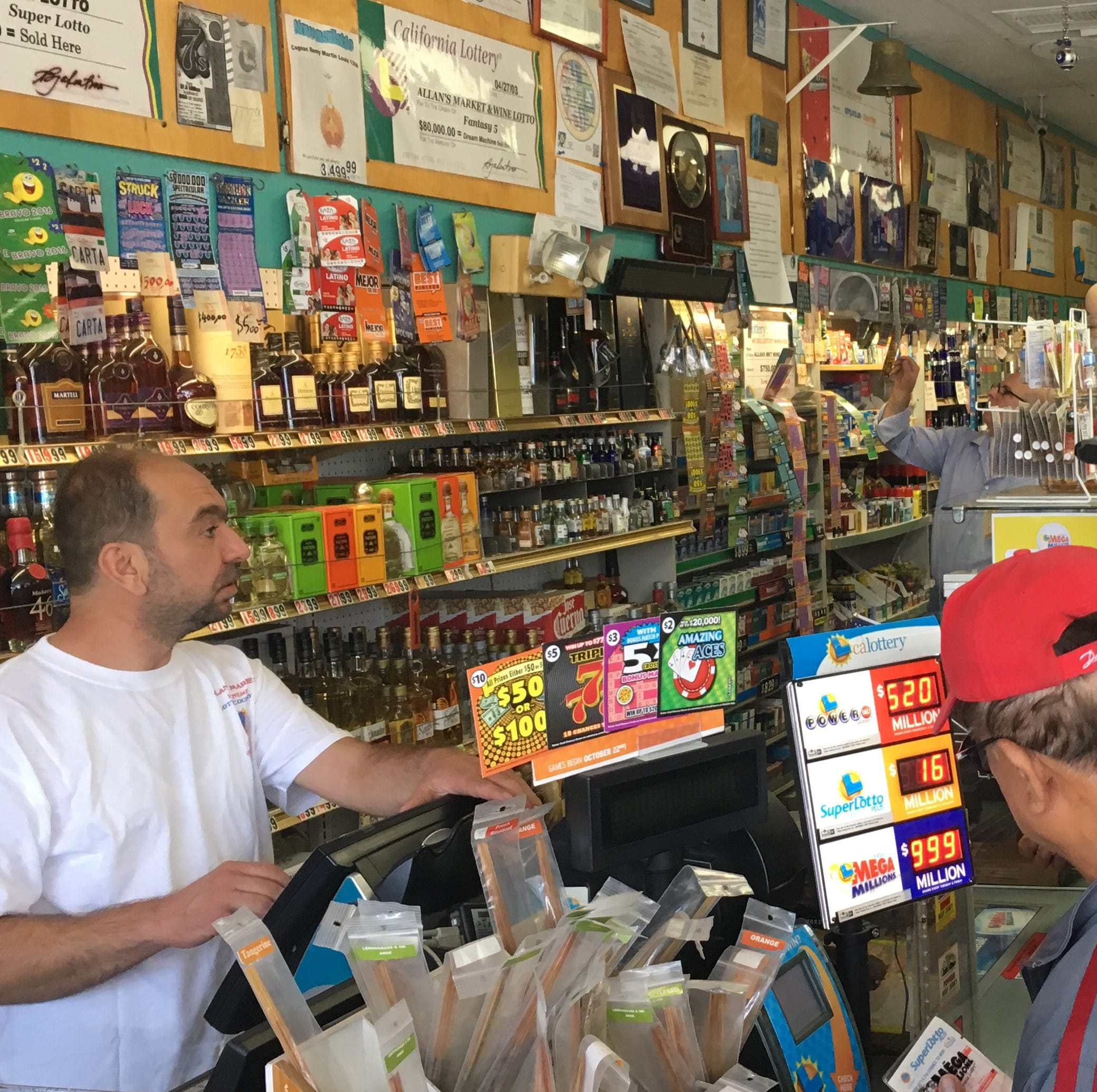 Samer Roubboz sells lottery tickets to a steady stream of customers at Allan's Market Wine & Lotto in Port Hueneme.