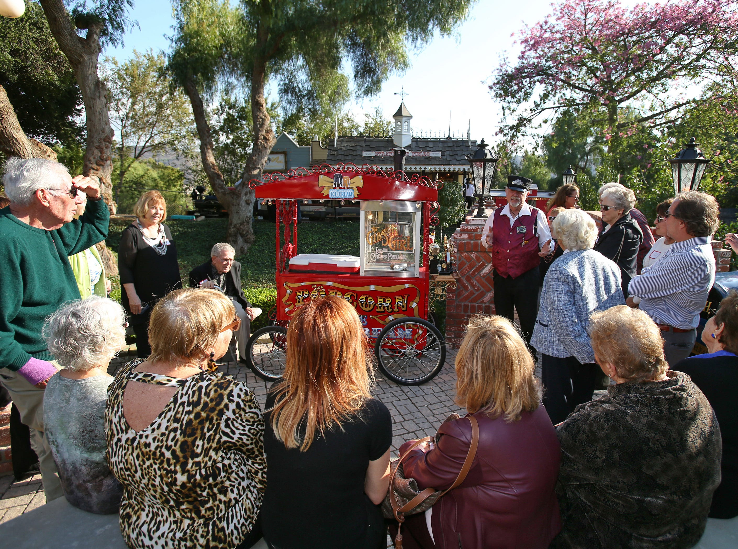 Mike Newlon gives a brief history of the popcorn cart that he purchased from the Playboy Manson as guests from the California Museum of Art Thousand Oaks head toward the train station on the property. A steam train and a replica of Disneyland's Main Street Trolley share the tracks at the Santa Rosa Valley home.