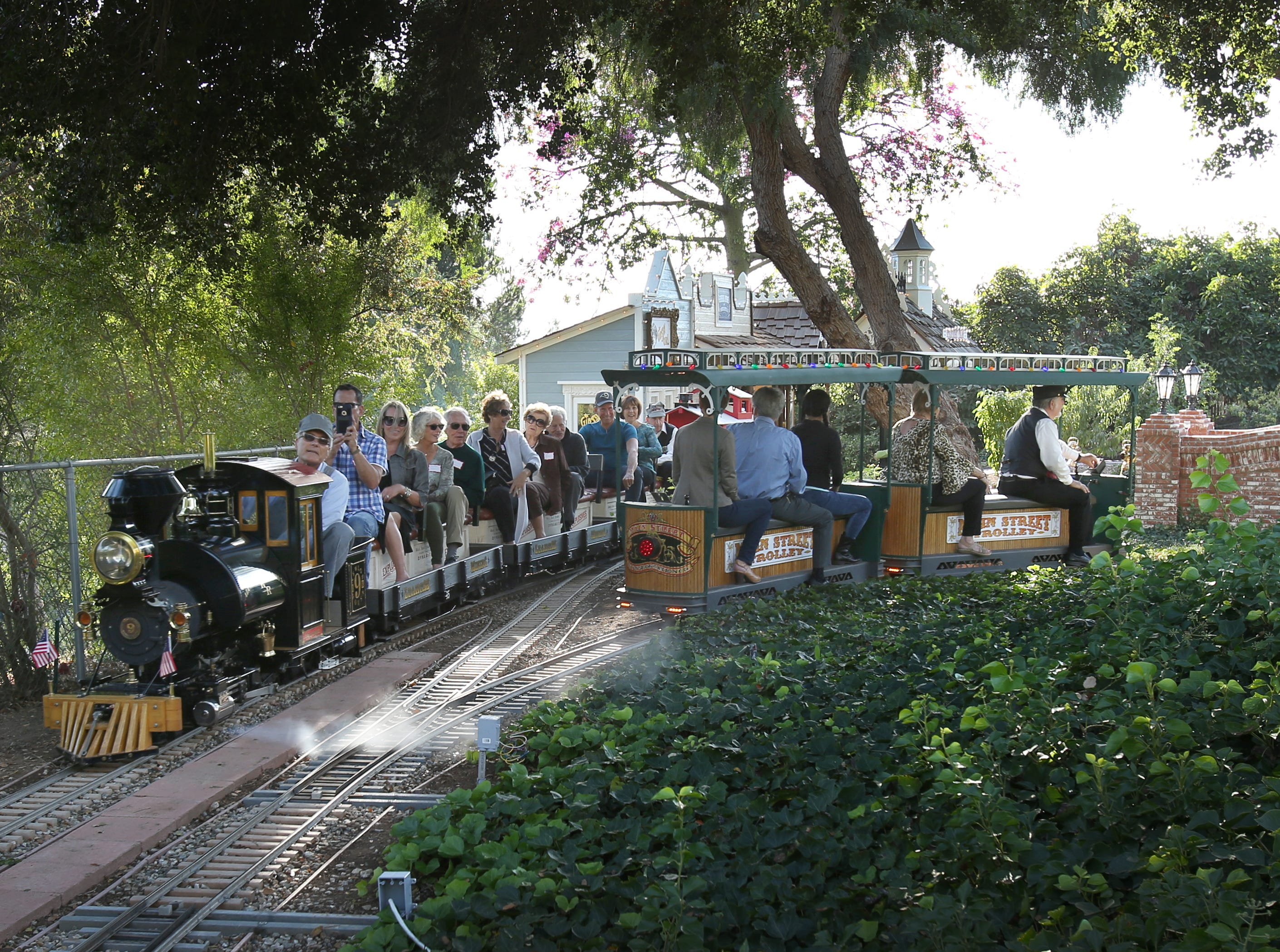 Guests from the California Museum of Art Thousand Oaks ride a steam train and a replica of a Disneyland Main Street Trolley during their tour of Mike and Lorraine Newlons' Victorian-style home in the Santa Rosa Valley. Piloting the train is Bryan Tapking, of Thousand Oaks, and piloting the trolley is owner Mike Newlon. The train and trolley also pass through a tunnel that Mike Newlon said was the first privately owned licensed tunnel in Ventura County.