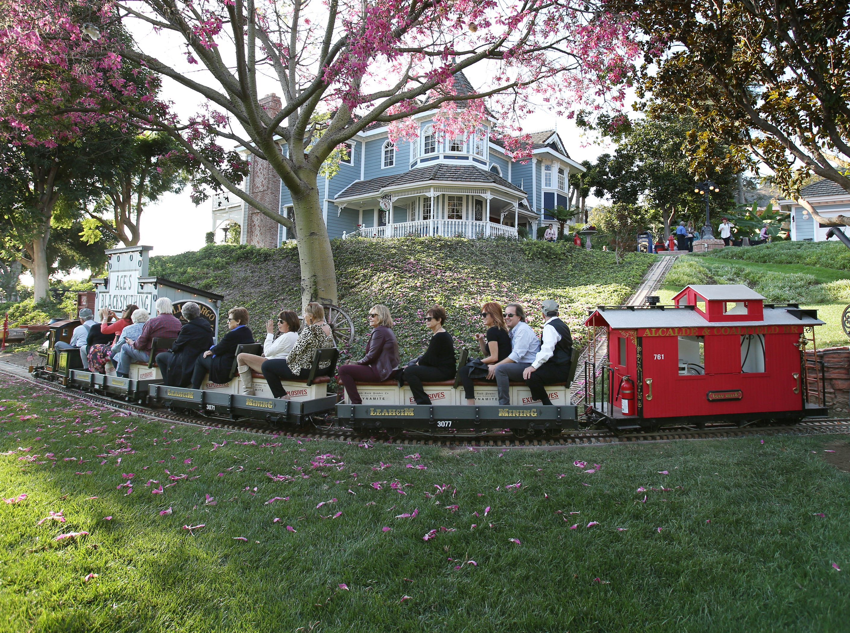 Guests from the California Museum of Art Thousand Oaks ride on a steam train as they tour the grounds of the Mike and Lorraine Newlon home in Santa Rosa Valley. Guests were also able to ride on a replica of Disneyland's Main Street Trolley that shared the same tracks as the train.