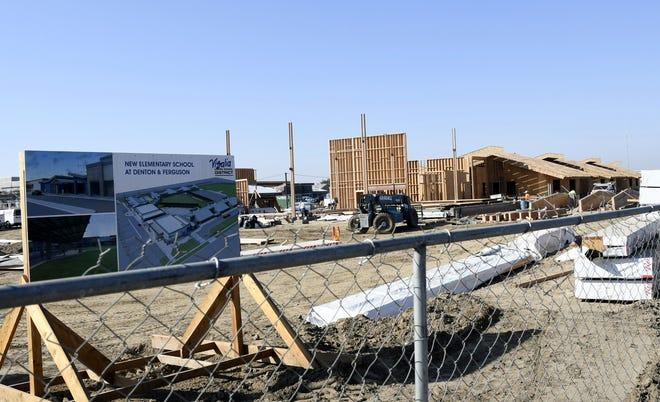 Construction crews work at Visalia Unified School District's new elementary school site on the corner of Ferguson Avenue and Denton Street on Monday, October 22, 2018.