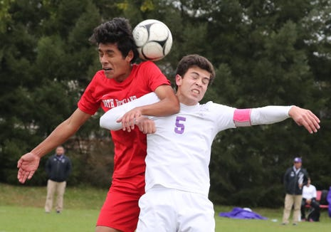 North Rockland's Brayan Paredes, left, goes up for the ball with New Rochelle's David Benko during their Class AA quarterfinal at North Rockland Oct. 20, 2018.