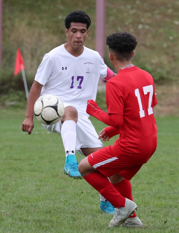 New Rochelle's Henry Valencia, left, is pressured by North Rockland's Jerry Garafalo during their Class AA quarterfinal at North Rockland Oct. 20, 2018.
