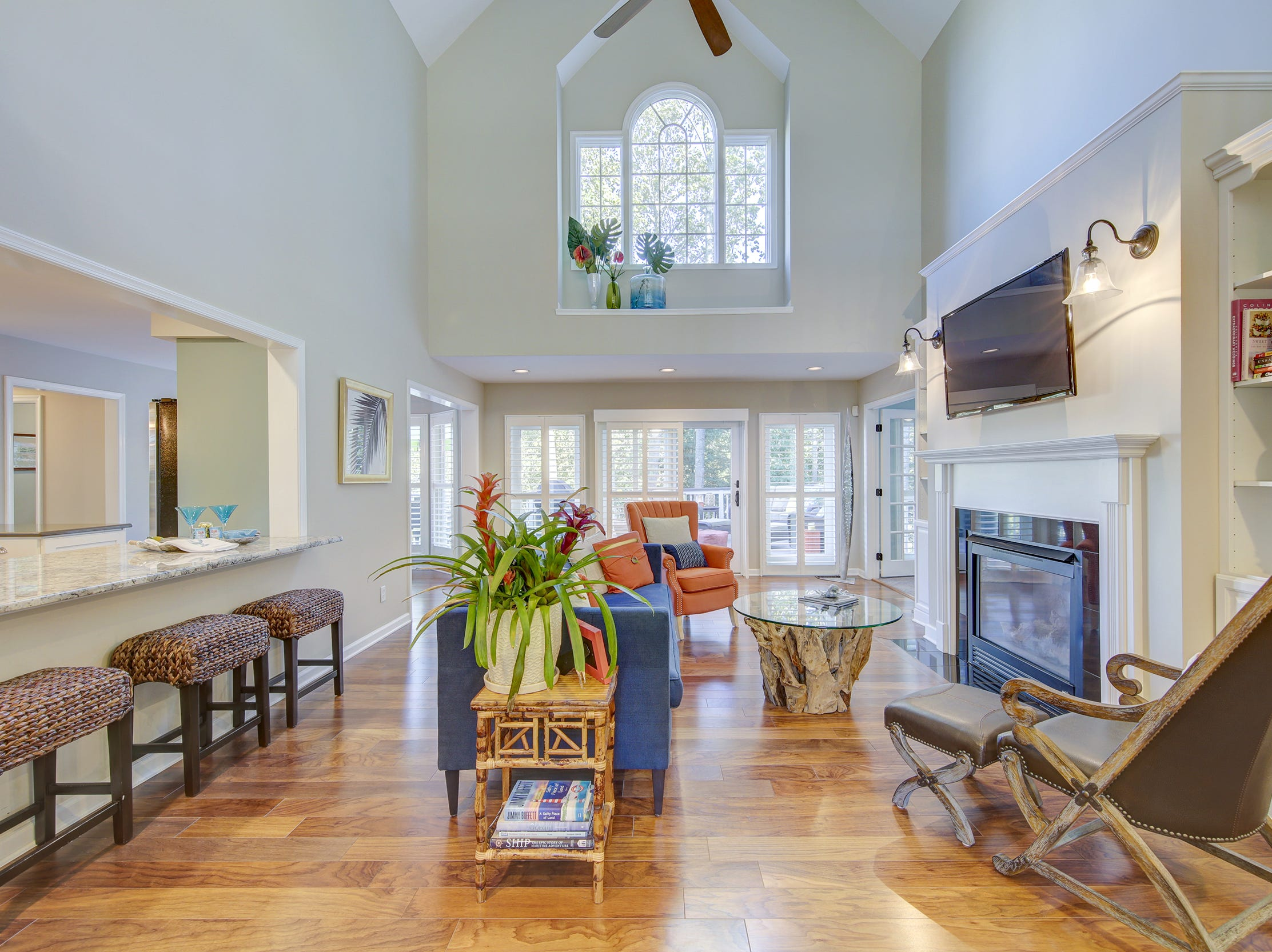 The gathering room at 204 Lakeview Shores is two stories tall and adjoins the kitchen and a screened porch.