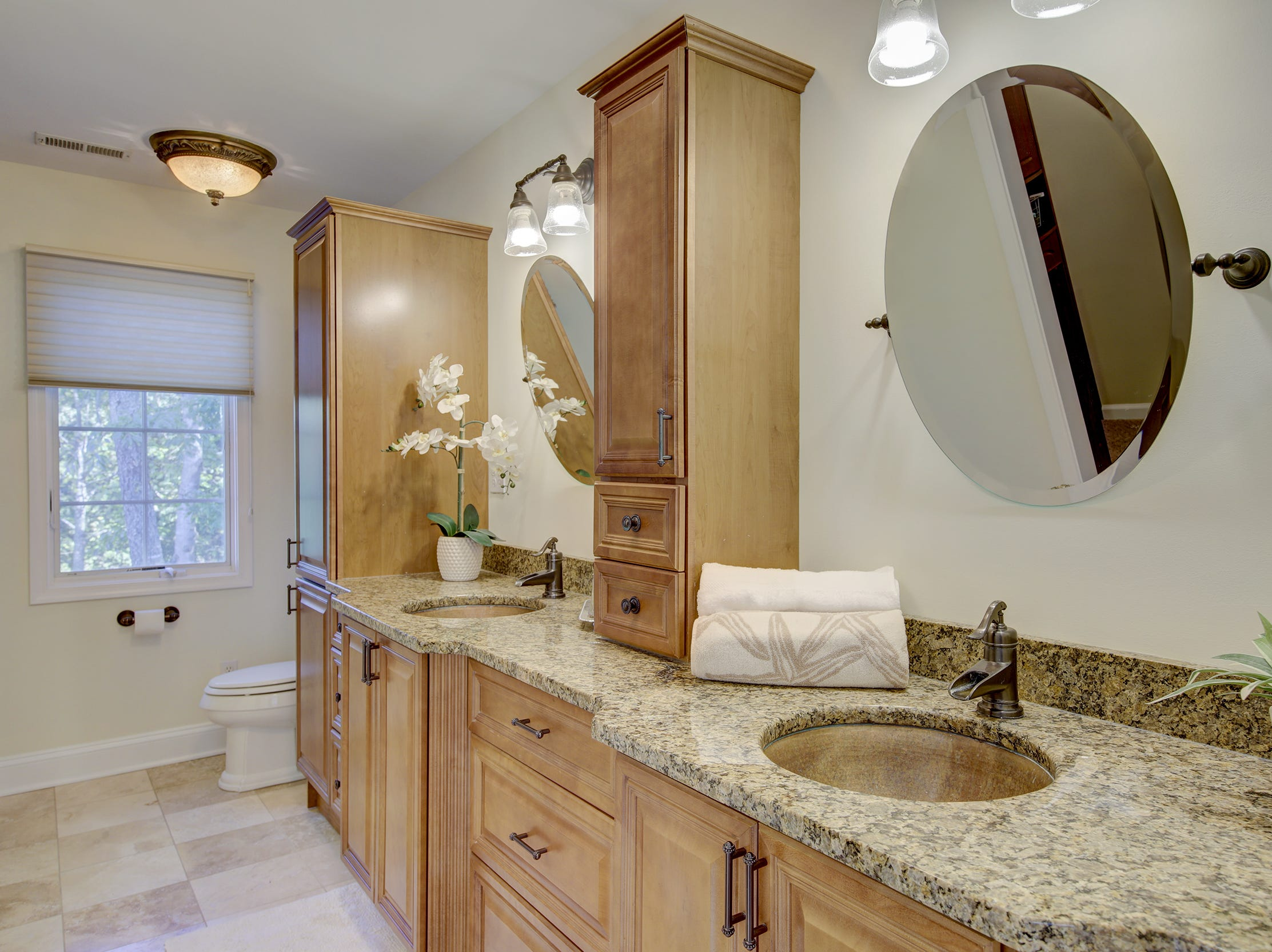 This bath at 204 Lakeview Shores  features dual vanities and wood cabinetry.