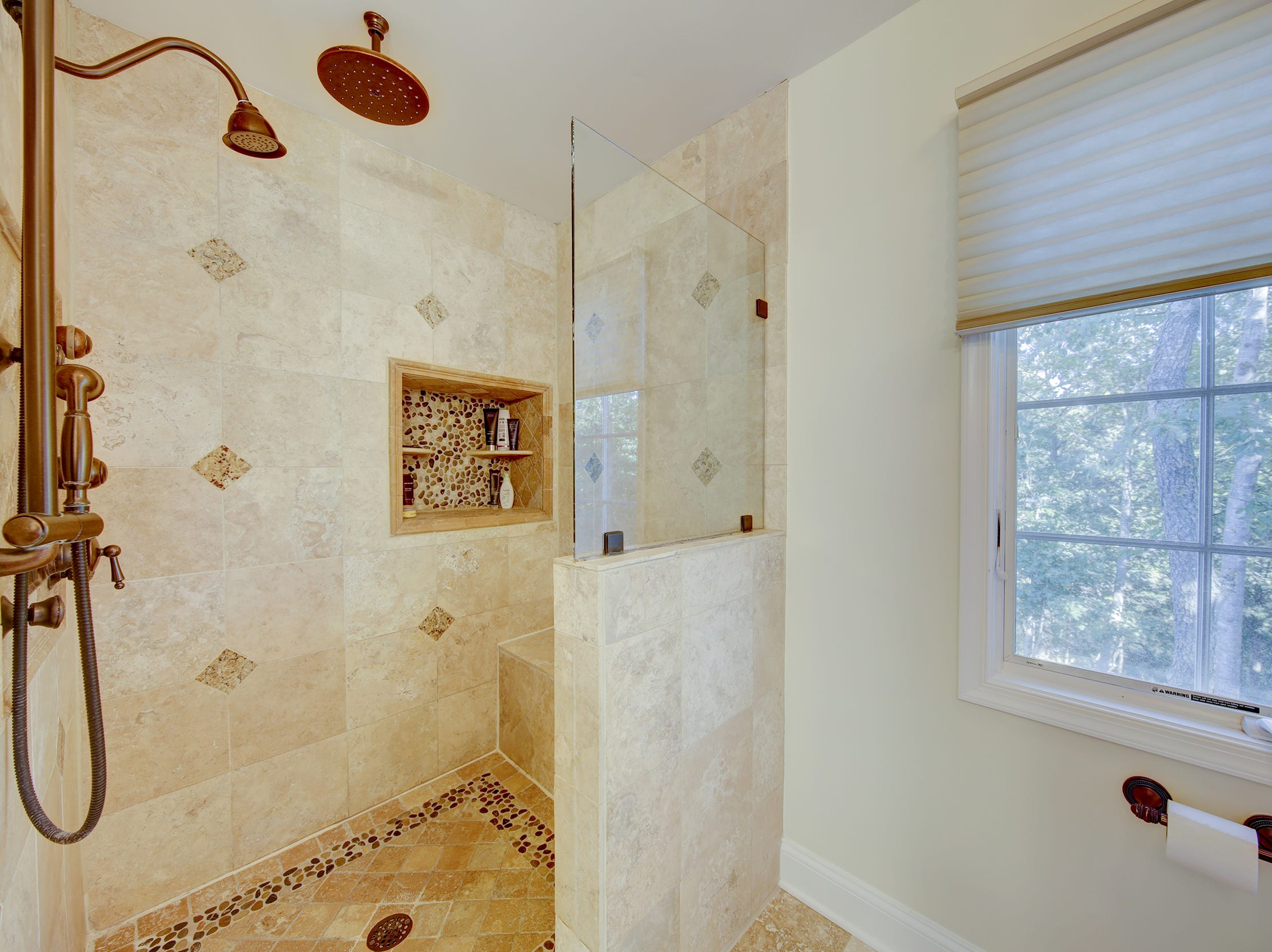 This bath at 204 Lakeview Shores in Rehoboth Beach has a rain head and custom tile work.