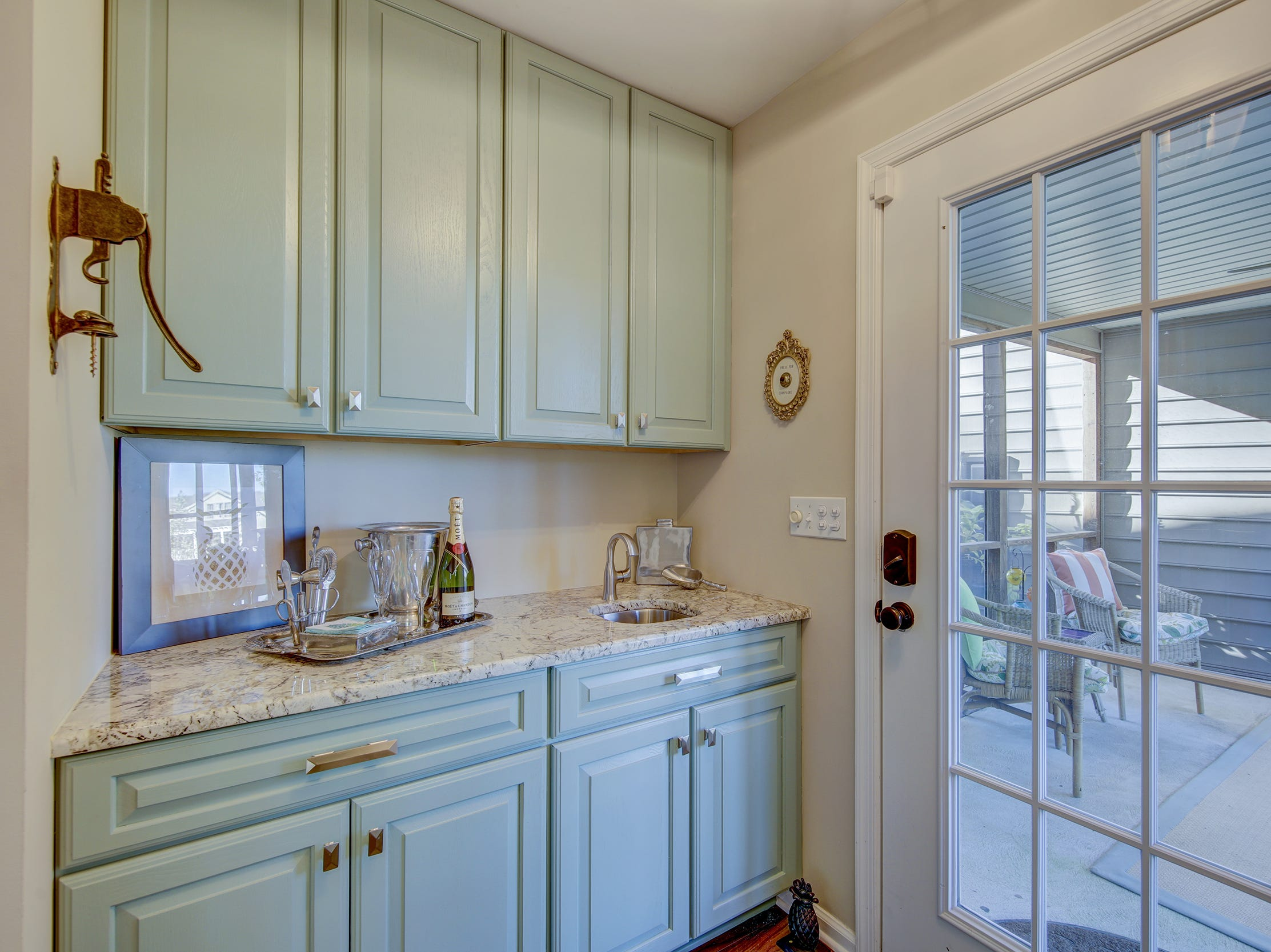 A bar area is sited between the kitchen and screened porch at 204 Lakeview Shores in Rehoboth Beach.