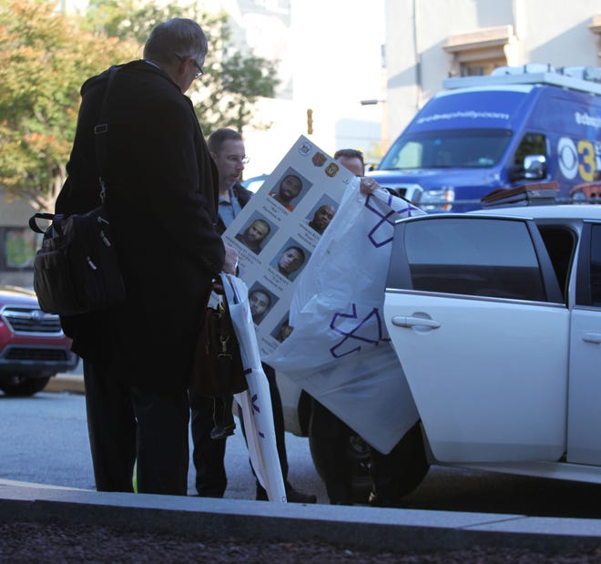 Prosecutors take posterboards out from the back of a vehicle before entering the New Castle County Courthouse at the beginning of the trial in October.