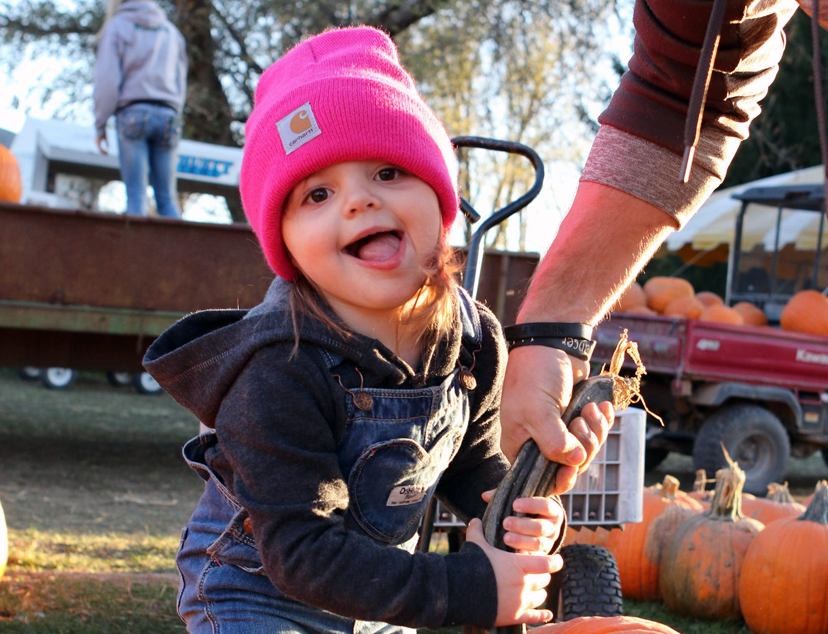 Ellie Bauer, 3, of Mukwonago, gets help lifing a pumpkin from dad, Greg, at Schuett Farms in Mukwonago on Oct. 22.
